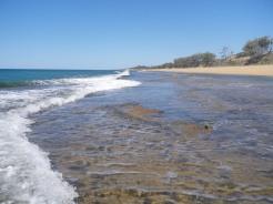 Waves break along the edge of Flat Rock